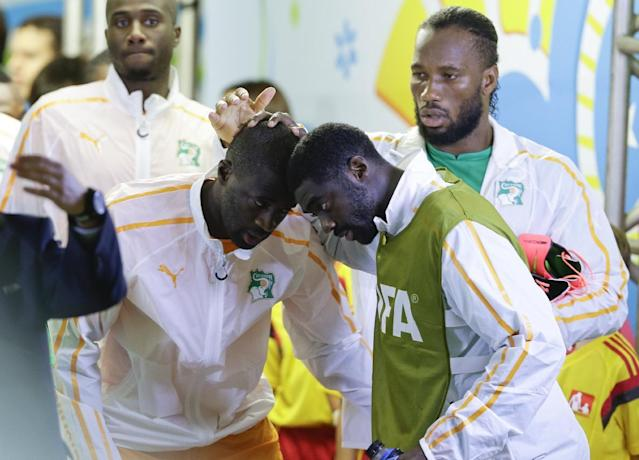 Ivory Coast's Kolo Toure and Yaya Toure, left, greet each other as Didier Drogba watches before the group C World Cup soccer match between Ivory Coast and Japan at the Arena Pernambuco in Recife, Brazil, Saturday, June 14, 2014. (AP Photo/Ricardo Mazalan)