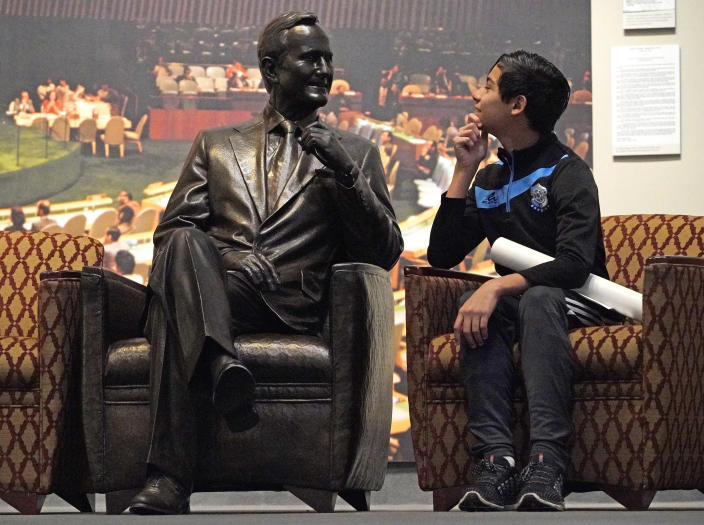 Andrew Lopez, 12, of Midland, Texas, sits next to a statue of George H.W. Bush inside the George H.W. Bush Presidential Library and Museum on Dec. 1, in College Station, Texas. (Photo: David J. Phillip/AP)