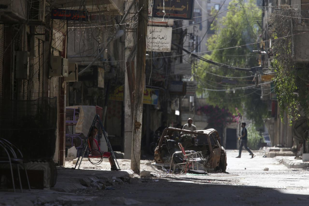 A girl (L) rests on a swing along a damaged street in Ain Tarma, in Eastern Ghouta, a suburb of Damascus August 21, 2014. A year passed since the chemical attacks on Eastern Ghouta of Damascus. REUTERS/Bassam Khabieh (SYRIA - Tags: POLITICS CIVIL UNREST CONFLICT)