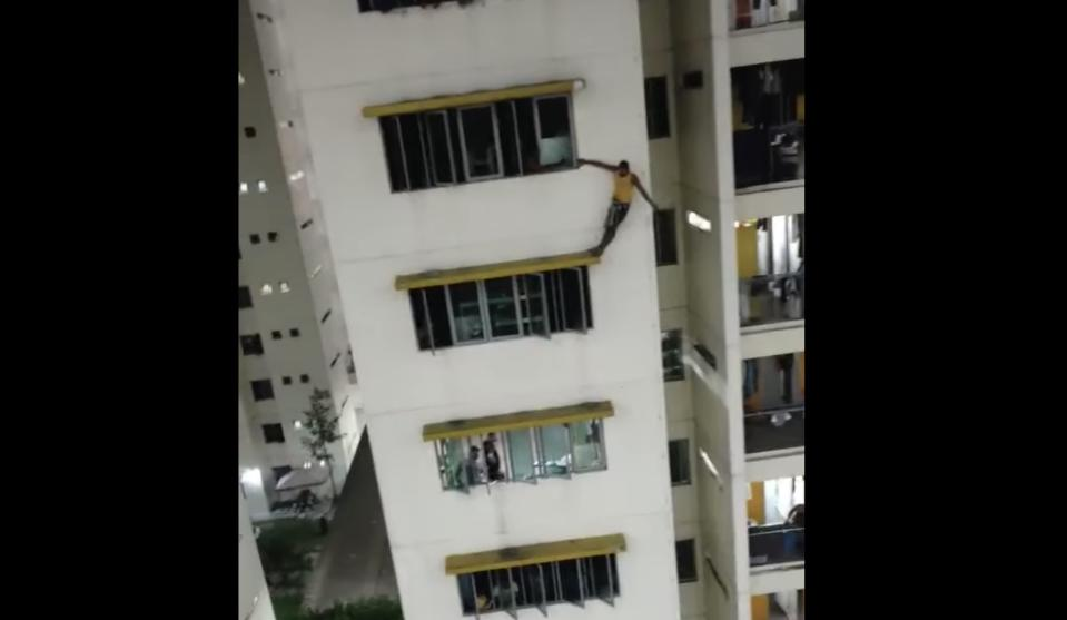A man was apprehended by police for standing on window ledge at a migrant workers dormitory in Kaki Bukit. (PHOTO: Screenshot/Facebook)