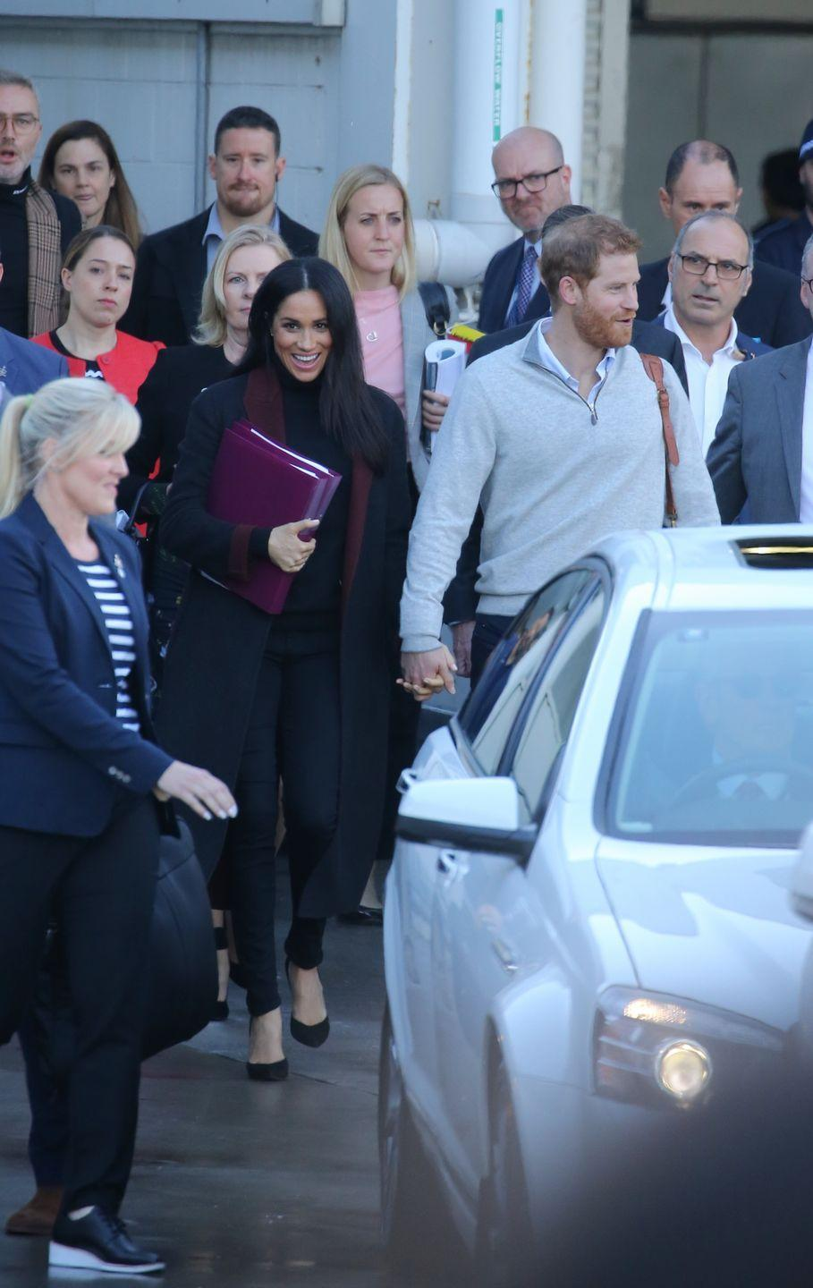 """<p>Prince Harry and Meghan Markle touched down in Sydney for <a href=""""https://www.townandcountrymag.com/society/tradition/a21273366/meghan-markle-prince-harry-first-royal-tour-2018/"""" rel=""""nofollow noopener"""" target=""""_blank"""" data-ylk=""""slk:their royal tour"""" class=""""link rapid-noclick-resp"""">their royal tour </a>with some news to share: <a href=""""https://www.townandcountrymag.com/society/tradition/a23773992/meghan-markle-pregnant-first-royal-baby-prince-harry/"""" rel=""""nofollow noopener"""" target=""""_blank"""" data-ylk=""""slk:the Duchess is pregnant!"""" class=""""link rapid-noclick-resp"""">the Duchess is pregnant!</a> Meghan wore a black coat with a maroon trim for the occasion, with a black turtleneck and matching pants. </p>"""