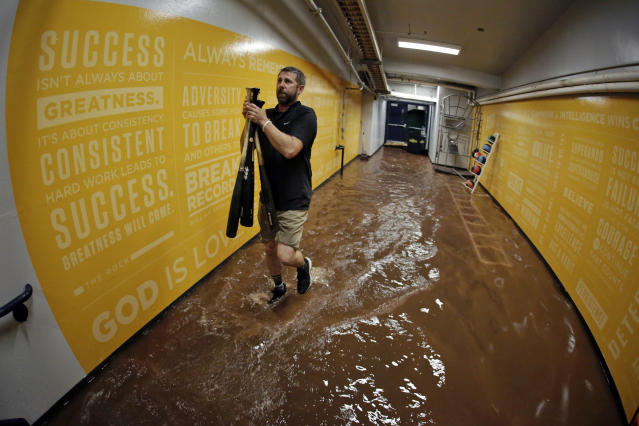 Pittsburgh Pirates clubhouse attendant Scott Bennett carries bats through a flooded tunnel from the dugout after a baseball game between the Pittsburgh Pirates and the Milwaukee Brewers was postponed because of heavy rain, Wednesday, June 20, 2018, in Pittsburgh. (AP Photo/Gene J. Puskar)
