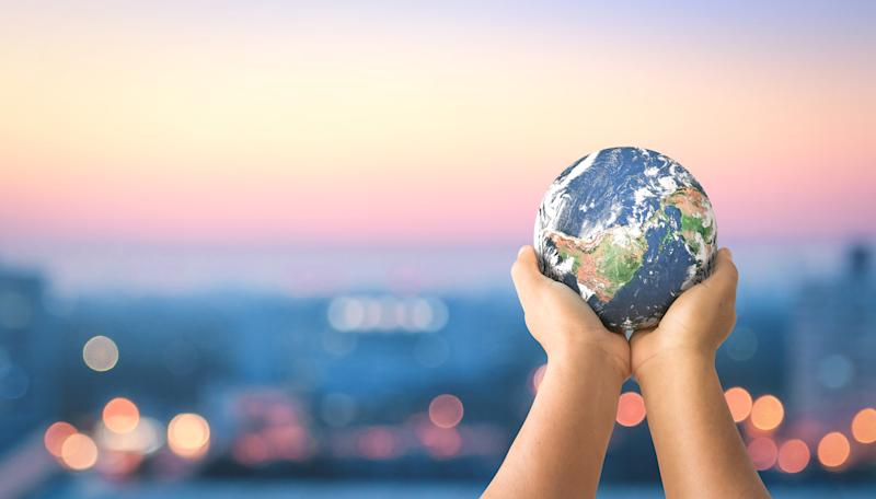 Child's hands holding up a small globe.