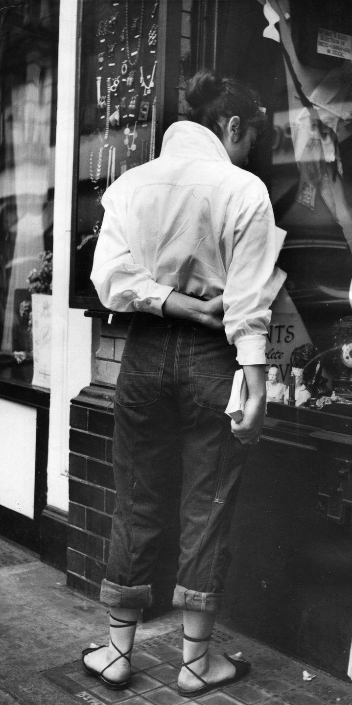 <p>By now jeans were really picking up steam for fashionable women, and women across the pond, too. Here, an early street style image of a young woman window shopping in London's Piccadilly neighborhood.</p>