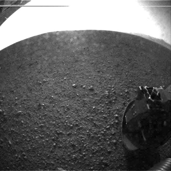 This photo provided by NASA's Jet Propulsion Laboratory shows the gravel on the surface of Mars' Gale Crater where the Curiosity rover landed late Sunday, Aug. 5, 2012 PDT. On the horizon is the rim of the crater. Part of the spring that released the lens' dust cover can be seen at the bottom right, near the rover's wheel. At top left is part of the rover's power supply. The lines across the top are an artifact from the sensor since the camera is looking into the sun. (AP Photo/NASA/JPL-Caltech)
