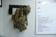 Tactical gear and a whiteboard hang over the cot where Capt. Michael Switzer sleeps in his office at Camp Beauregard in Pineville, La., Friday, July 30, 2021. (AP Photo/Gerald Herbert)
