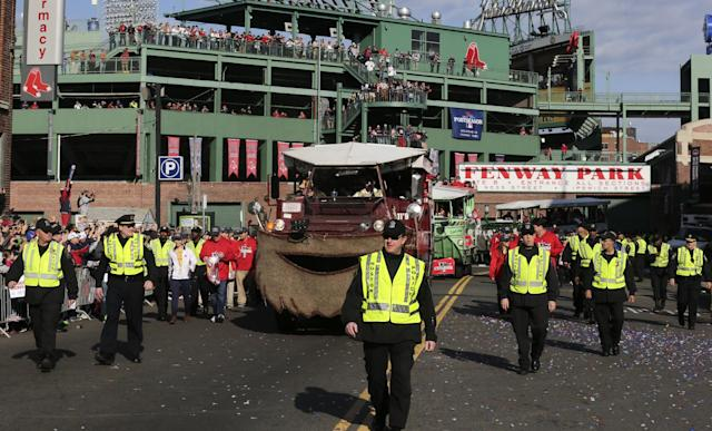 Police flank duck boats carrying Boston Red Sox players away from Fenway Park during a rolling parade in celebration of the baseball team's World Series win, Saturday, Nov. 2, 2013, in Boston. (AP Photo/Charles Krupa)