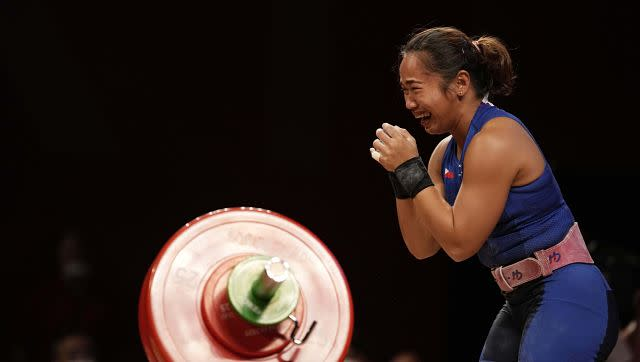 Hidilyn Diaz of Philippines celebrates as she sets the new world record and wins the gold medal in the women's 55kg weightlifting event. AP