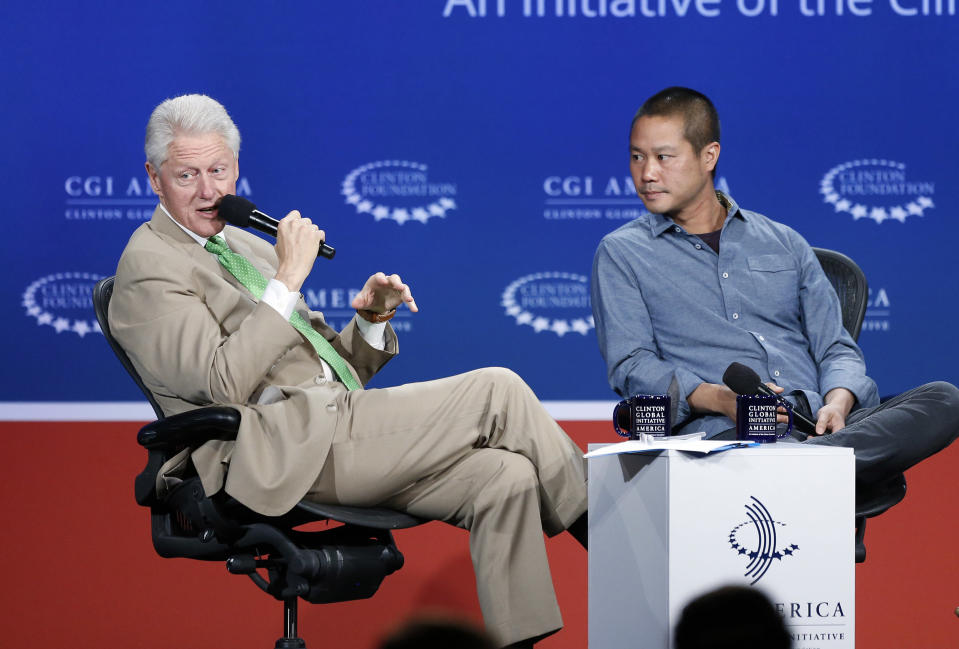 FILE - In this June 25, 2014, file photo, former President Bill Clinton, left, speaks with Zappos.com CEO Tony Hsieh during a forum on the final day of the annual gathering of the Clinton Global Initiative America in Denver. Hsieh, retired CEO Zappos.com, has died. Hsieh was with family when he died Friday, Nov. 27, 2020, according to a statement from DTP Companies, which he founded. Downtown Partnership spokesperson Megan Fazio says Hsieh passed away in Connecticut, KLAS-TV reported. Hsieh recently retired from Zappos after 20 years leading the company. He worked to revitalize the Las Vegas area. (AP Photo/Brennan Linsley, File)
