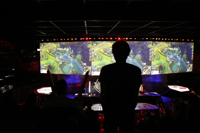 A man stands in the rows during the final of League of Legends tournament between Team G2 Esports and Team FunPlus Phoenix, in Paris, Sunday, Nov. 10, 2019. The biggest e-sports event of the year saw a Chinese team, FunPlus Phoenix, crowned as world champions of the video game League of Legends. Thousands of fans packed a Paris arena for the event, which marked another step forward for the growing esports business. (AP Photo/Thibault Camus)