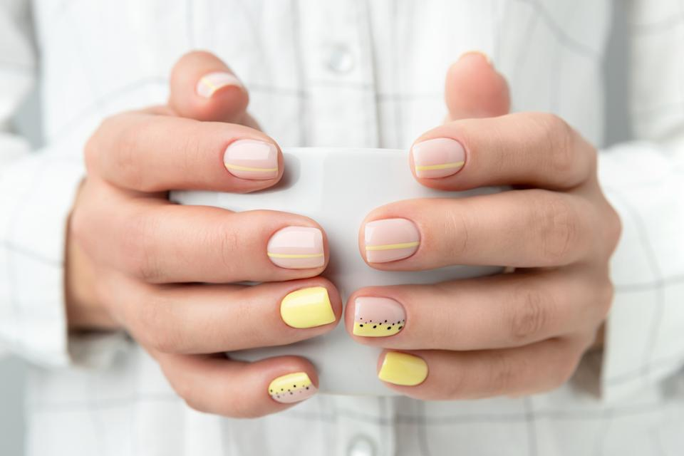 Manicured woman's hands holding a cup of coffee or tea.