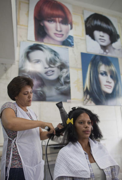 In this Feb. 4, 2013 photo, a stylist brushes the hair of a customer at a salon in Sao Paulo, Brazil. In 2008, L'Oreal opened a lab in Rio to focus on hair. Human hair falls into eight types depending on diameter, curliness, the number of waves, twists and other measures, and highly multiracial Brazil has all eight, unlike most countries in Europe, Asia or Africa, said Blaise Didillon, head of research and innovation for L'Oreal Brazil. (AP Photo/Andre Penner)