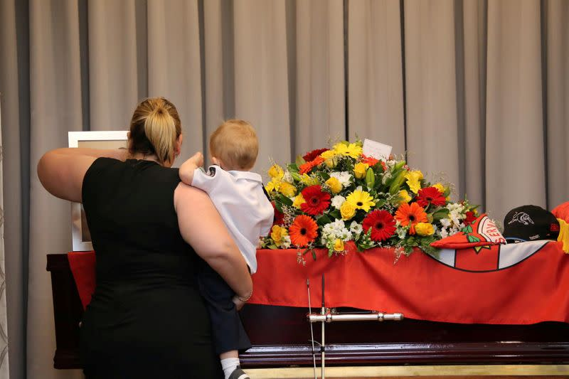 Mourners stand near the coffin of late RFS volunteer Keaton during his funeral in Buxton
