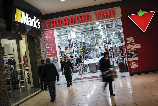 People walk out of a Canadian Tire Store that is located by a Mark's clothing store, which is owned by Canadian Tire Corporation in Toronto, May 8, 2014. (Reuters)