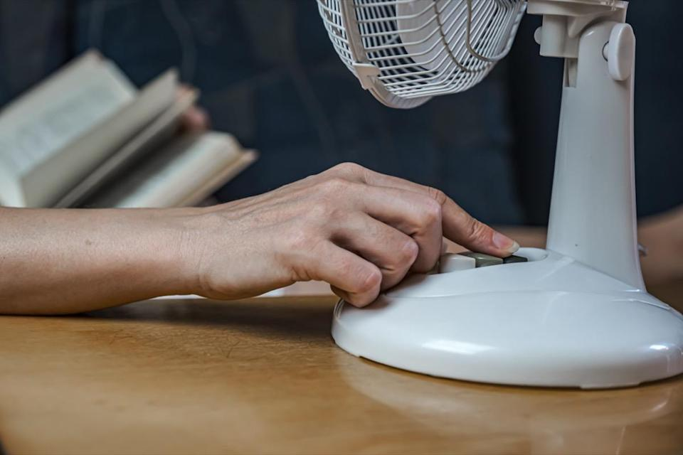 A woman's hand turns on the fan.