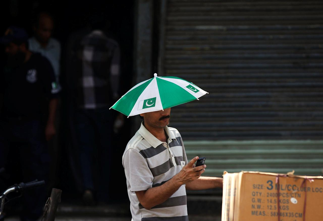 A man with a small umbrella on his head to avoid sunlight during intense heatwave, while busy on mobile phone along a market in Karachi, Pakistan May 23, 2018. REUTERS/Akhtar Soomro