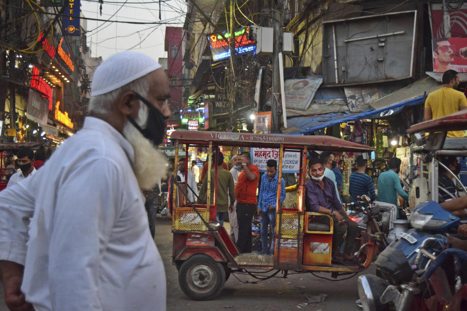 A driver of an e-rickshaw waits for passengers at a busy market place in New Delhi, India, Sunday, March 28, 2021. India has ambitions to expand use of electric vehicles to wean itself from polluting fossil fuels, but EVs are still a rarity on its congested highways. A lack of charging stations and poor quality batteries are discouraging drivers from switching over. (AP Photo/Neha Mehrotra)
