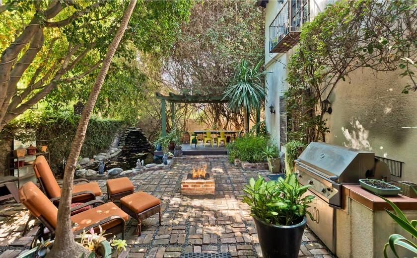 Built in 1923, the two-story home features Spanish-style living spaces and a dramatic backyard with ponds, dining areas and fire features.