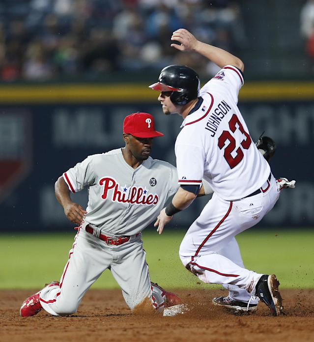 Atlanta Braves' Chris Johnson (23) steals second base as Philadelphia Phillies shortstop Jimmy Rollins (11) applies the late tag in the third inning of a baseball game in Atlanta, Friday, July 18, 2014. (AP Photo/John Bazemore)