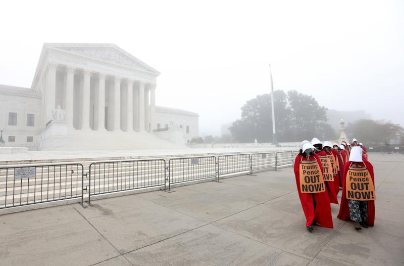 """On a foggy morning, protesters with the """"Handmaids Brigade"""" march outside the Supreme Court prior to a hearing held by the Senate Judiciary Committee to vote on the nomination of Judge Amy Coney Barrett on October 22, 2020, in Washington, D.C."""