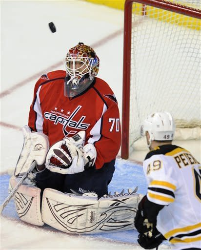 Washington Capitals goalie Braden Holtby (70) keeps his eye on the puck as Boston Bruins right wing Rich Peverley (49) watches during the first period of Game 3 of an NHL hockey Stanley Cup first-round playoff series, Monday, April 16, 2012, in Washington. (AP Photo/Nick Wass)
