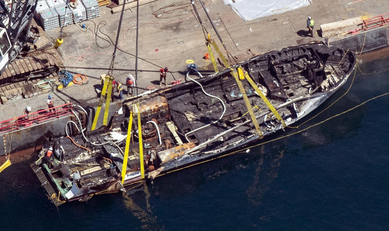 FILE - In this Sept. 12, 2019, file photo, the burned hull of the Conception is brought to the surface by a salvage team off Santa Cruz Island in the Santa Barbara Channel in Southern California. The family of the lone crew member to die in a fiery scuba boat disaster that killed all 33 passengers off the Southern California coast last year sued the vessel's owner Monday, Jan. 13, 2020, in federal court. The lawsuit by the family of Allie Kurtz claims the owners of the Conception knew the boat was unsafe and lacked required smoke detectors and fire equipment. (Brian van der Brug/Los Angeles Times via AP, File)