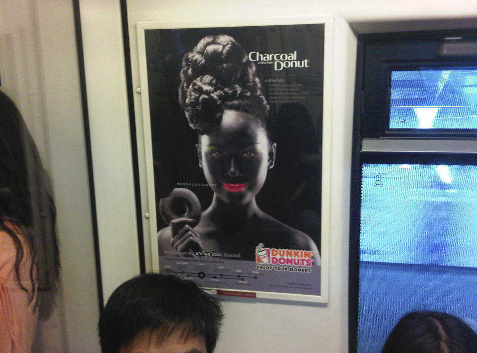 """<p> An advertisement poster of a smiling woman with bright pink lips in blackface makeup holding a doughnut is seen on a Skytrain, a commuter train in Bangkok, Thailand, Friday, Aug. 30, 2013. A leading human rights group has called on Dunkin' Donuts to withdraw the """"bizarre and racist"""" advertisement for chocolate doughnuts in Thailand. The Dunkin' Donuts franchise in Thailand launched a campaign earlier this month for its new """"Charcoal Donut"""" featuring the image, which is reminiscent of 19th and early 20th century American stereotypes for black people that are now considered offensive symbols of a racist era. (AP Photo/Grant Peck)</p>"""