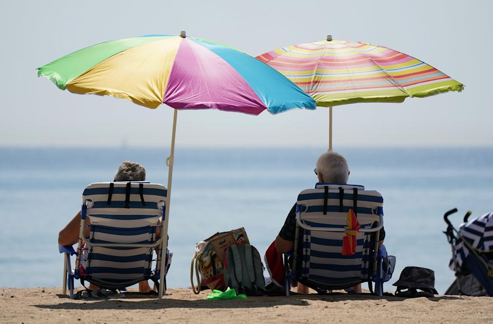 People sit under umbrallas as they enjoy the hot weather at Bournemouth beach (Andrew Matthews/PA) (PA Wire)