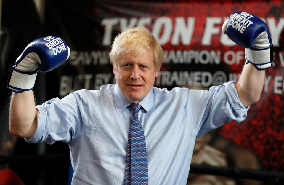 """Britain's Prime Minister and leader of the Conservative Party, Boris Johnson wears boxing gloves emblazoned with """"Get Brexit Done"""" as he poses for a photograph at Jimmy Egan's Boxing Academy in Manchester north-west England on November 19, 2019, during a general election campaign trip. - Britain will go to the polls on December 12, 2019 to vote in a pre-Christmas general election. (Photo by Frank Augstein / various sources / AFP) (Photo by FRANK AUGSTEIN/AP/AFP via Getty Images)"""