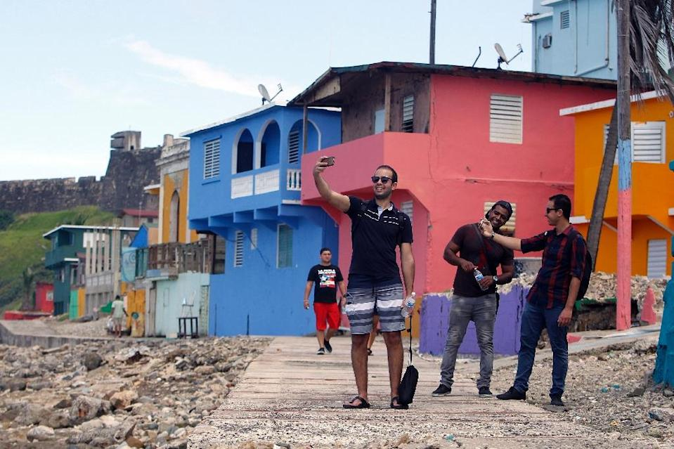 "A man takes a selfie with friends in La Perla area where the video for ""Despacito"" was recorded in San Juan, on July 22, 2017 (AFP Photo/Ricardo ARDUENGO)"
