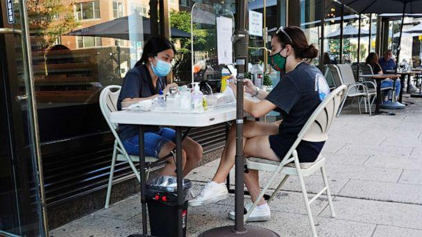 PHOTO: A woman wearing a protective mask gets a manicure at an outside station at a nail salon as the city continues Phase 4 of re-opening following restrictions imposed to slow the spread of coronavirus on August 8, 2020 in New York City. (Cindy Ord/Getty Images)
