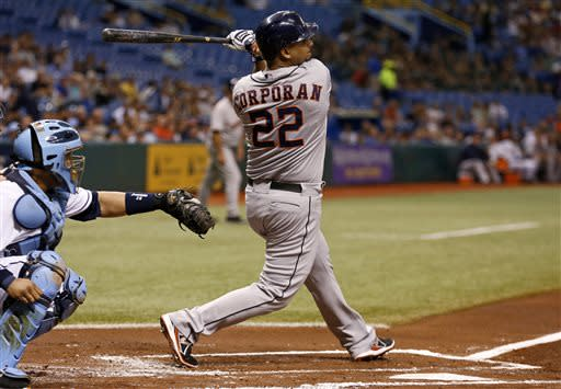 Houston Astros' Carlos Corporan (22) follows through on a single that knocked in two runs in front of Tampa Bay Rays catcher Jose Molina during the first inning of a baseball game, Friday, July 12, 2013, in St. Petersburg, Fla. (AP Photo/Mike Carlson)
