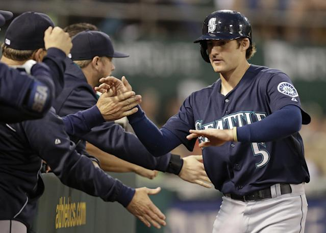Seattle Mariners' Brad Miller, right, is congratulated after scoring against the Oakland Athletics in the third inning of a baseball game Tuesday, Sept. 2, 2014, in Oakland, Calif. Miller scored on a single by Austin Jackson. (AP Photo/Ben Margot)