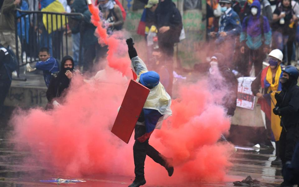 Demonstrators clash with riot police during a protest against President Ivan Duque's government at the Bolivar square in Bogota - JUAN BARRETO/AFP