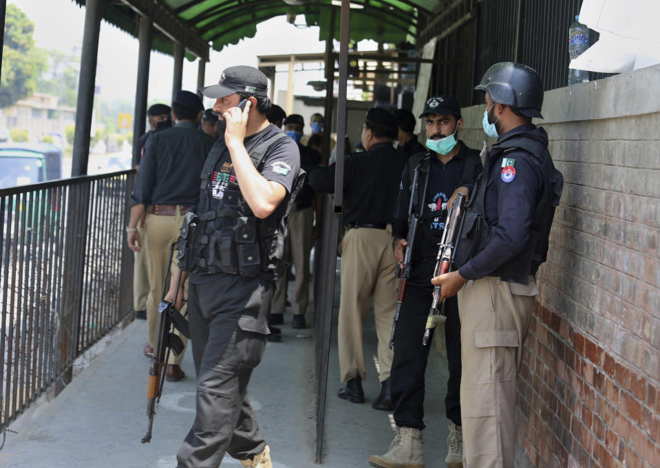 FILE - Police officers gather at an entry gate of district court following the killing of Tahir Shamim Ahmad, who was in court accused of insulting Islam, in Peshawar, Pakistan, Wednesday, July 29, 2020. Tahir Shamim Ahmad was a U.S. citizen, according to a U.S. State Department statement. (AP Photo/Muhammad Sajjad)