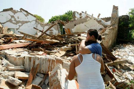 Women hug while standing next to a destroyed house after an earthquake struck the southern coast of Mexico late on Thursday, in Union Hidalgo, Mexico September 9, 2017. REUTERS/Jorge Luis Plata