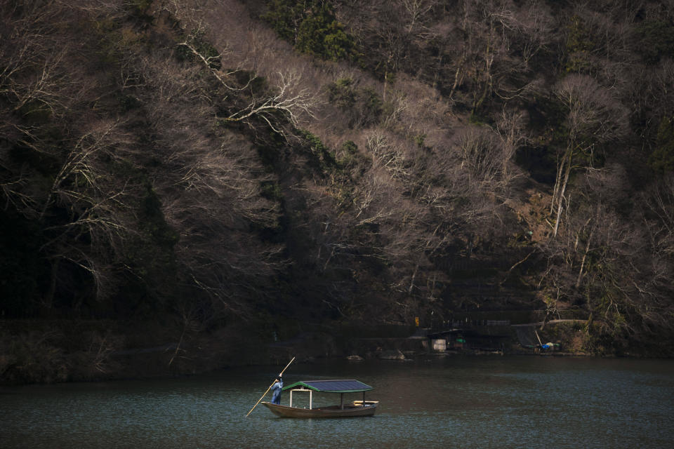 A boatman glides his boat across the river in the Arashiyama district of Kyoto, Japan, March 18, 2020. Widening travel restrictions and closures of most tourism and entertainment venues have gutted the tourism industry in many parts of the world, as well as in Japan. (AP Photo/Jae C. Hong)