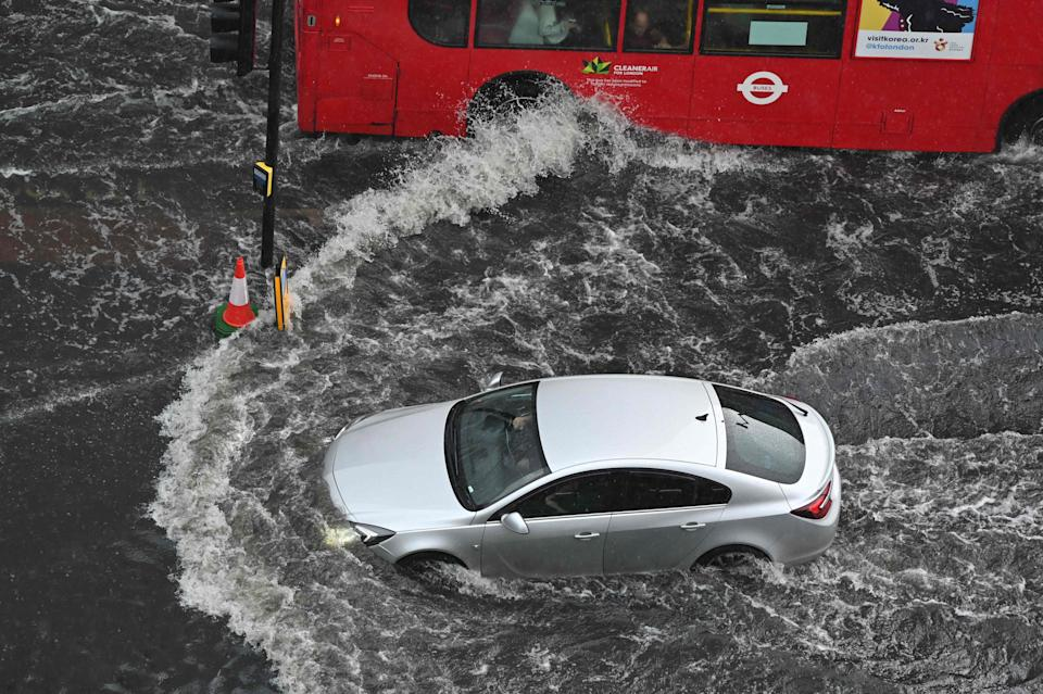 A car and a bus drive through deep water in Nine Elms on Sunday (AFP via Getty Images)