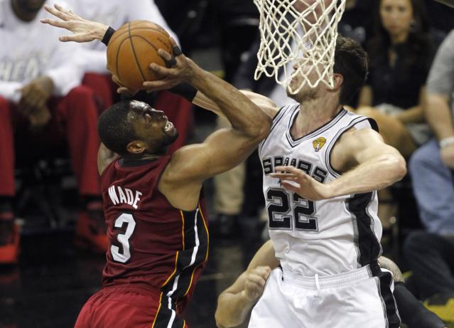 Miami Heat's Dwyane Wade (L) goes up to shoot against San Antonio Spurs' Tiago Splitter of Brazil in Game 1 of their NBA Finals basketball series in San Antonio, Texas June 5, 2014. REUTERS/Mike Stone (UNITED STATES - Tags: SPORT BASKETBALL)