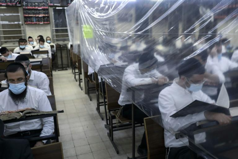 Ultra-Orthodox Jewish men study in a hall divided with plastic sheets to help stem the spread of Covid-19