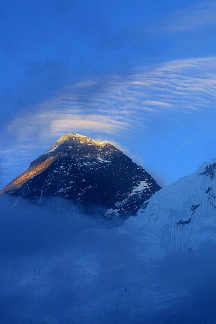 """FILE – In this May 26, 2003 file photo, the 8,850-meter (29,035-foot) Mount Everest is seen from above Everest Base Camp, Nepal. The Everest climbing season began March 2014, with new rules that require climbers to bring down at least eight kilograms (17.6 pounds) of their personal garbage, and more security officials at the mountain's base camp to help climbers. More than 4,000 climbers have scaled the summit since it was conquered in 1953 by Edmund Hillary and his Sherpa guide Tenzing Norgay. Over the years, climbers have left tons of garbage on the slopes on the mountain, and some have called it the """"world's highest garbage dump."""" (AP Photo/Gurinder Osan, File)"""