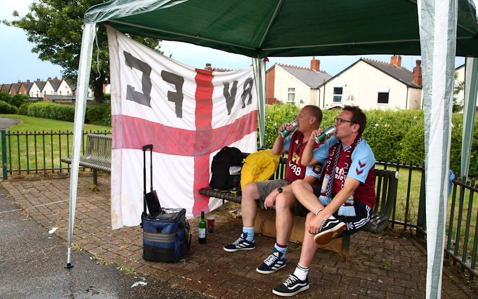 Father and son, Mark and Glen Goodwin prepare to watch the English Premier League football match between Aston Villa and Sheffield United which is taking place behind closed doors, in a Gazebo they have set up near Villa Park stadium - AFP