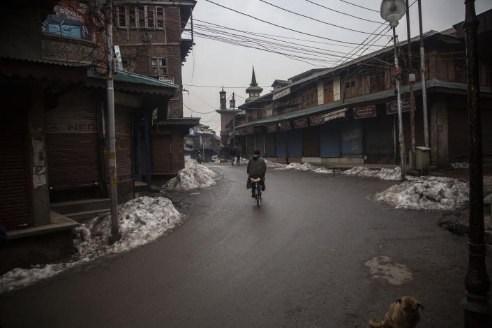 A Kashmiri man rides a bicycle through a closed market in Srinagar, Indian controlled Kashmir, Tuesday, Feb. 9, 2021. Businesses and shops have closed in many parts of Indian-controlled Kashmir to mark the eighth anniversary of the secret execution of a Kashmiri man in New Delhi. Hundreds of armed police and paramilitary soldiers in riot gear patrolled as most residents stayed indoors in the disputed region's main city of Srinagar. (AP Photo/Mukhtar Khan)