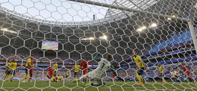 <p>England's Harry Maguire scores the opening goal past Sweden goalkeeper Robin Olsen </p>