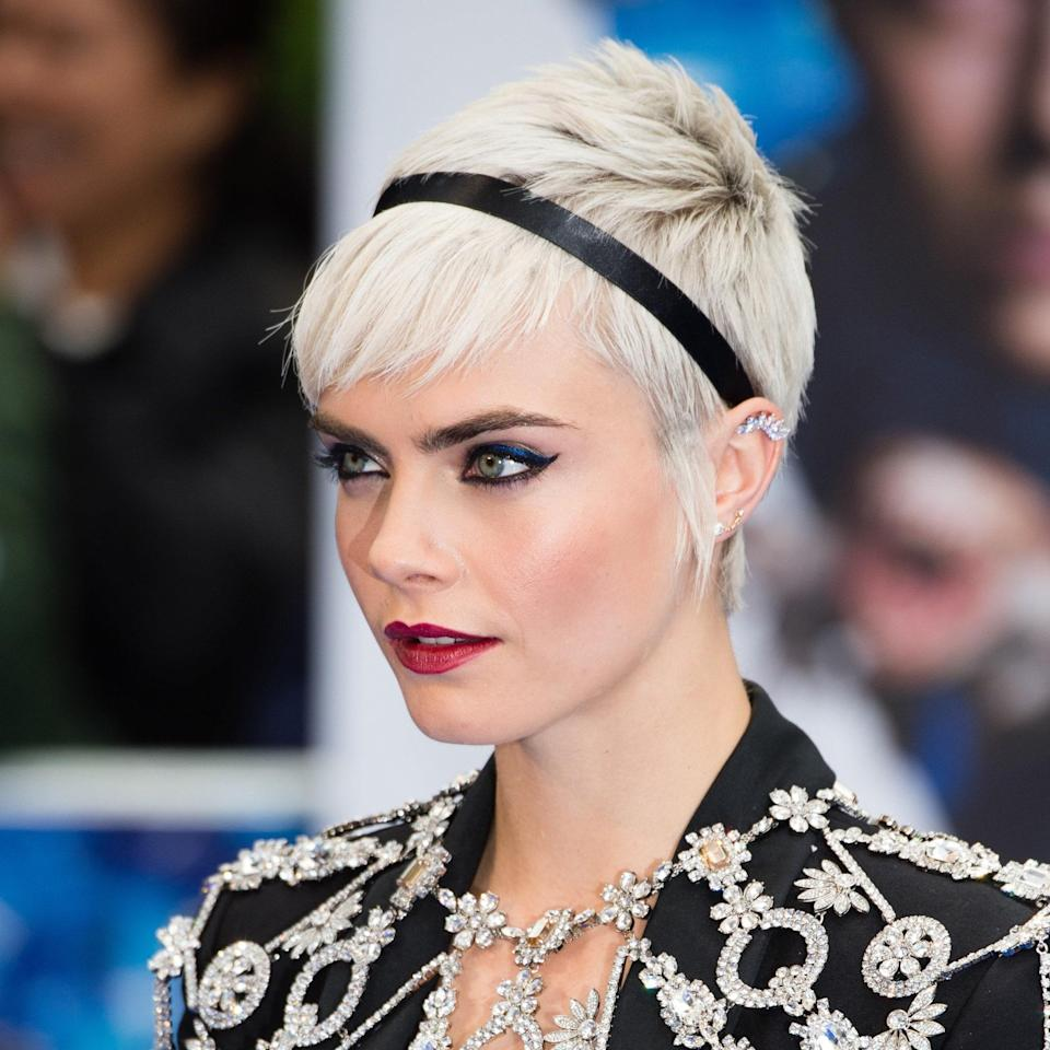 Maybe it's the platinum hair color, the black headband, or a combination of both that gives Cara Delevingne's look its edgy vibe. Complete with side bangs, this hairstyle exudes cool. Baxter notes this versatile look would pair well with a blazer decked in diamonds.