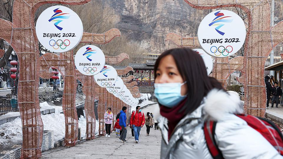 People wearing protective masks, pictured here in front the logos for the 2022 Beijing Winter Olympics.