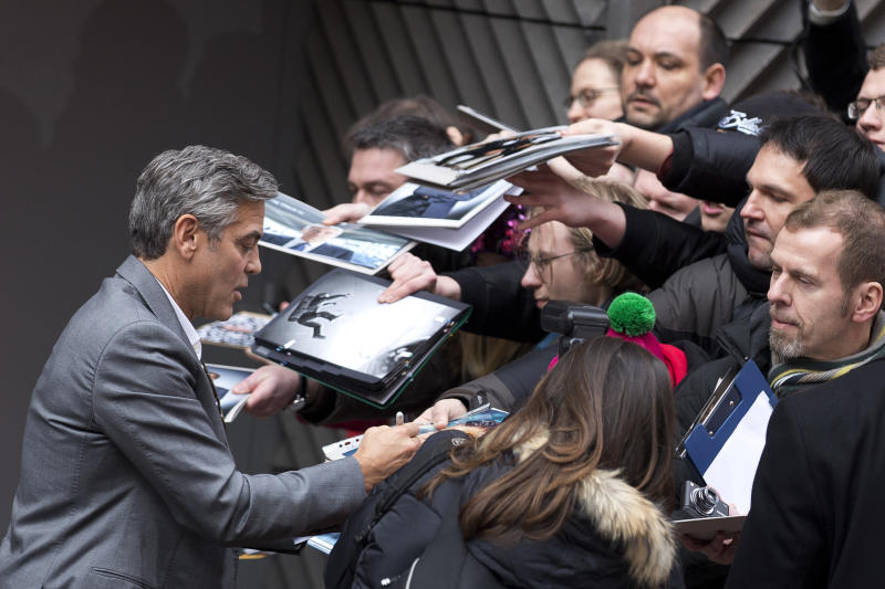 Actor George Clooney signs autographs for fans as he arrives for photo call of the film The Monuments Men during the International Film Festival Berlinale, in Berlin, Saturday, Feb. 8, 2014. (AP Photo/Axel Schmidt)