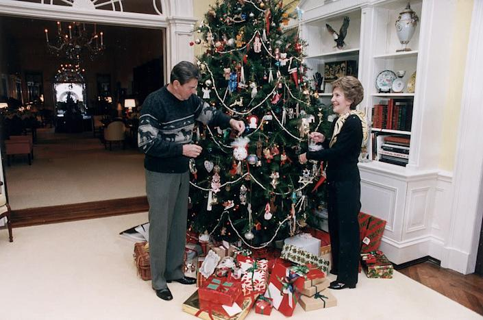 US President Ronald Reagan and First Lady Nancy Reagan decorate the White House Christmas tree, 24 December 1983. (Photo by Ronald Reagan Library/Getty Images) | Ronald Reagan Library—Getty Images
