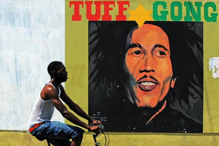 A man pedals past a mural of late reggae legend Bob Marley in Kingston, Jamaica