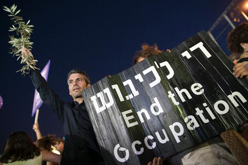 An Israeli left-wing supporter holds a banner during a mass demonstration tagged Two States, One Hope on May 27, 2017 in Tel Aviv (AFP Photo/JACK GUEZ)